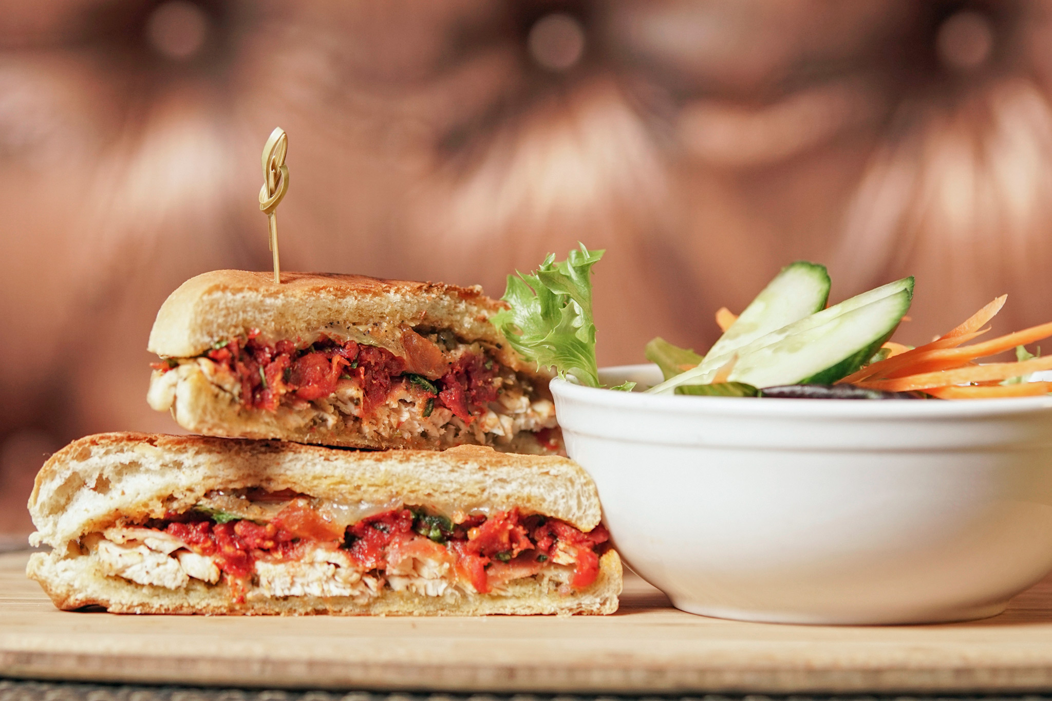 Chicken Panini - herb marinated grilled chicken breast, basil pesto, arugula and sun dried tomato relish, Tryst pepper sauce, toma cheese, prosciutto, ciabatta bun