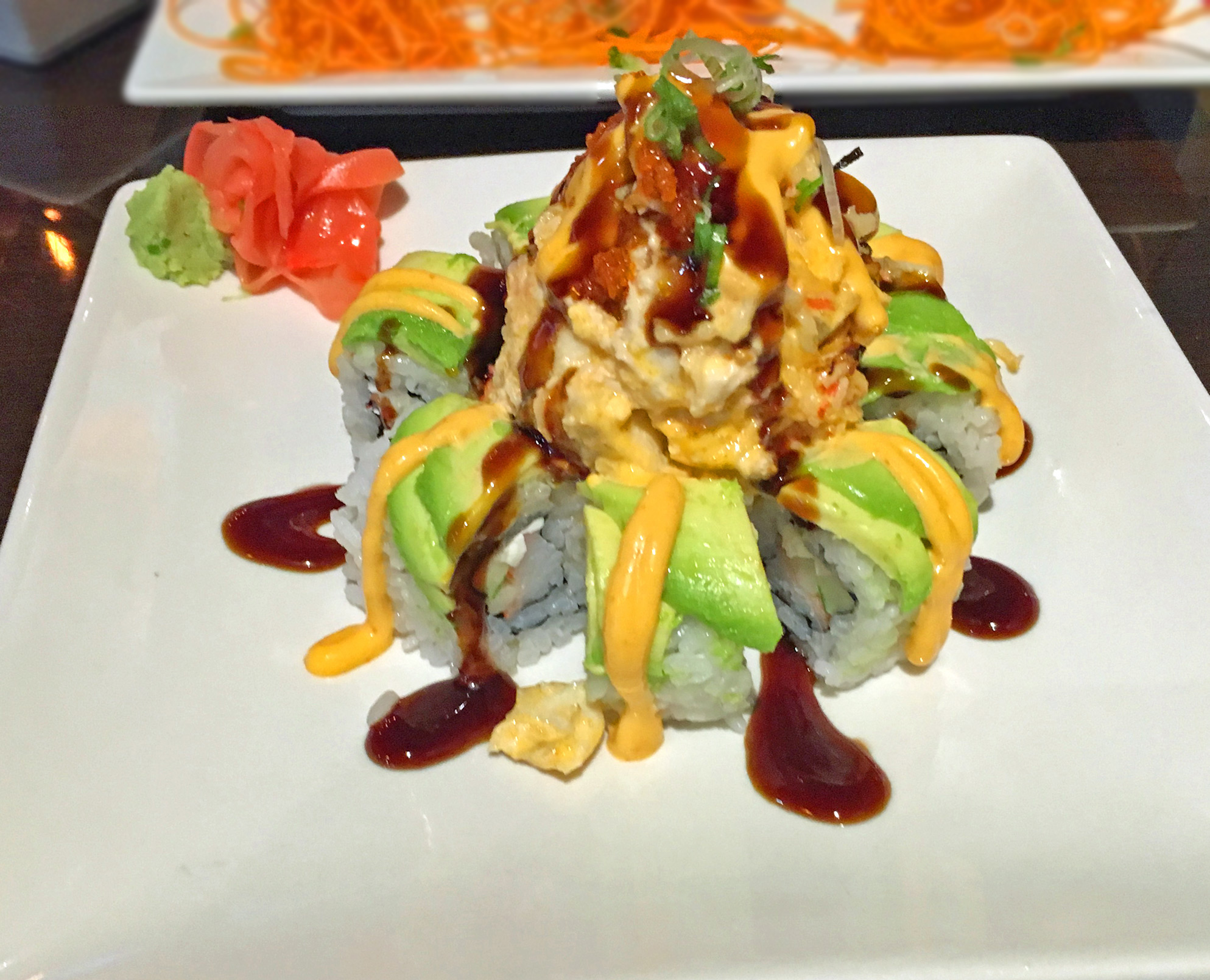 VESUVIUS AKA VOLCANO - Krab stick, cucumber and cream cheese roll topped with avocado, baked dynamite, eel sauce and spicy mayo