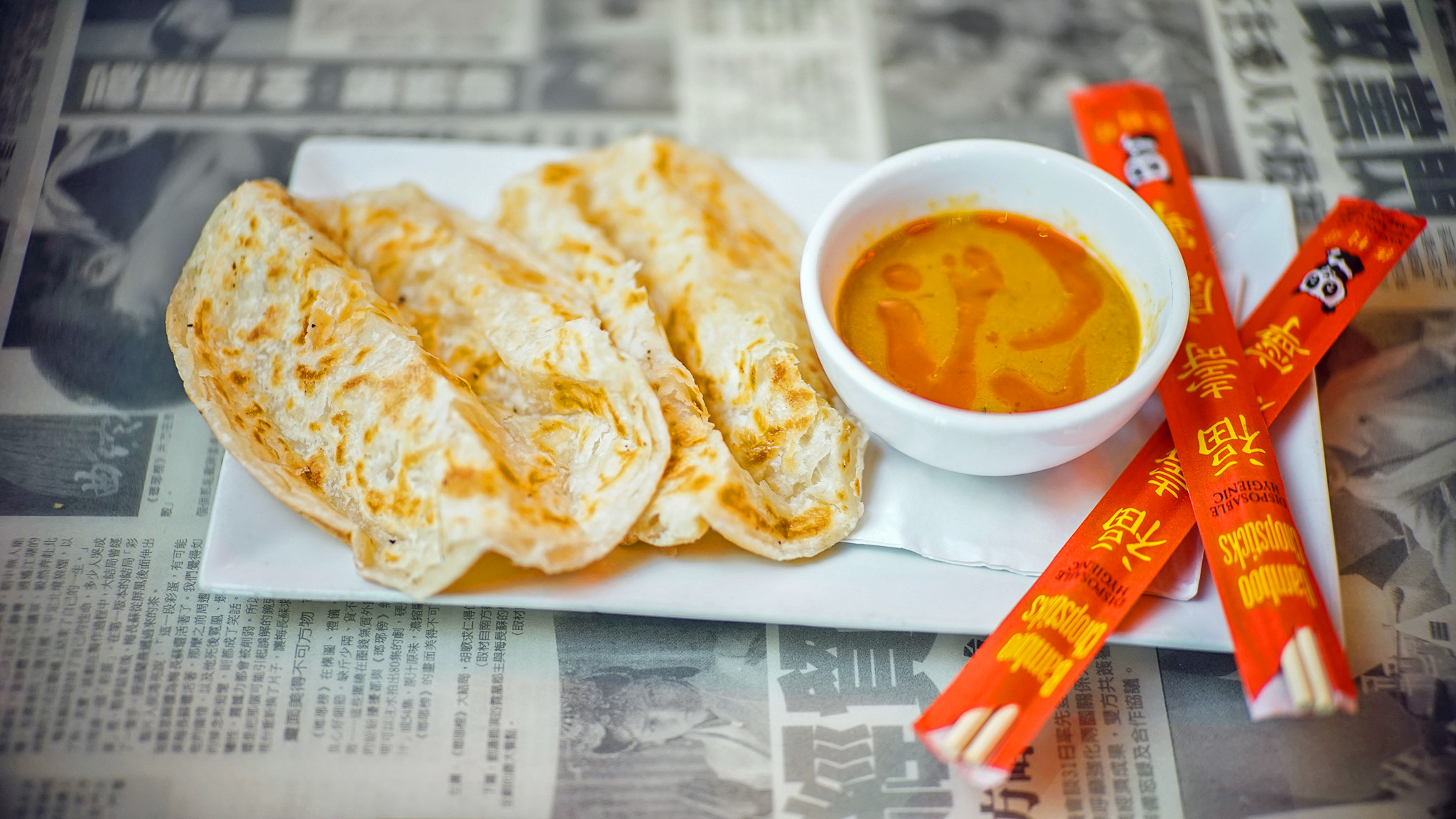 Roti Canai, which is a Malaysian flat bread served with a side of signature curry