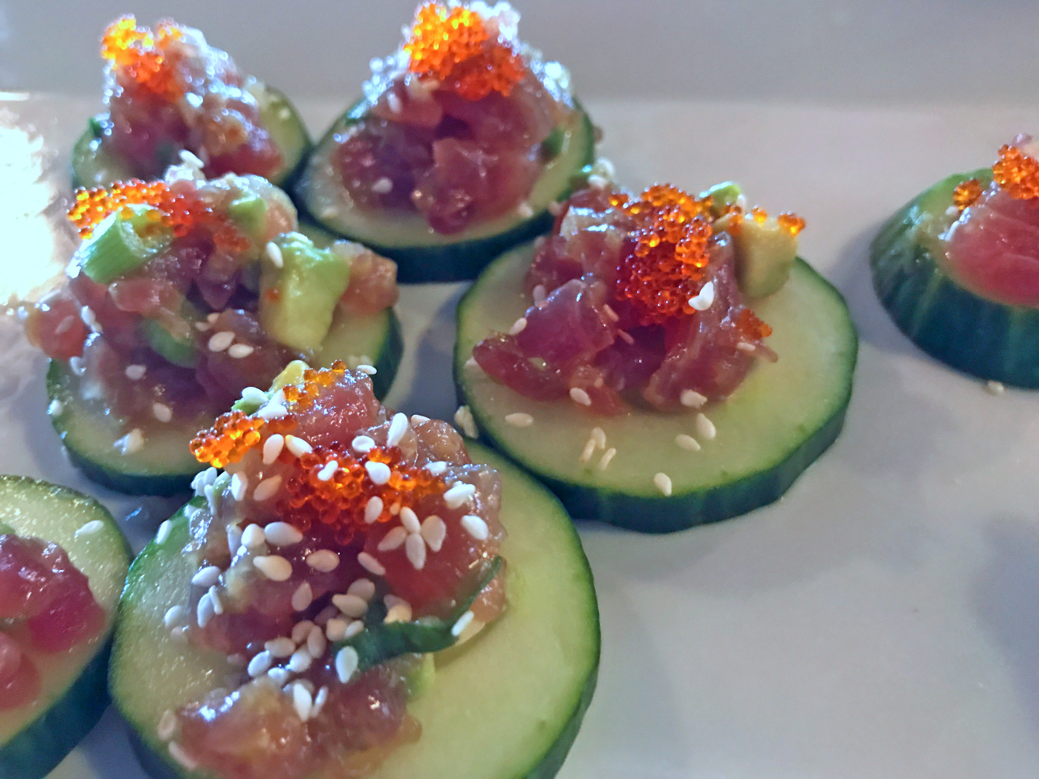 Ahi Tuna Poke // Sushi grade tuna tossed with avocado, sesame, soy, lime and sea salt. Served with tobiko, wontons and cucumber.