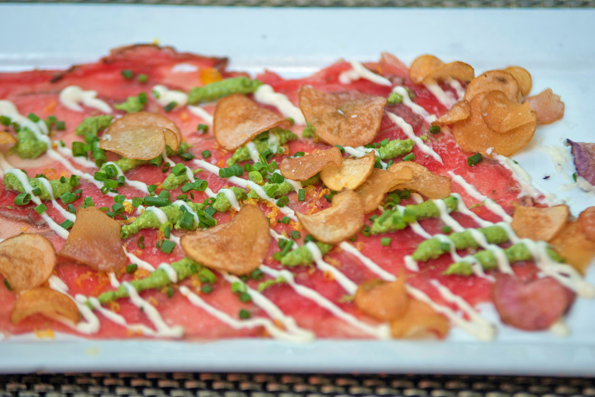 Bison Carpaccio - porcini crusted, cured yolk, house pesto, baby potato chips, garlic horsey sauce, chives