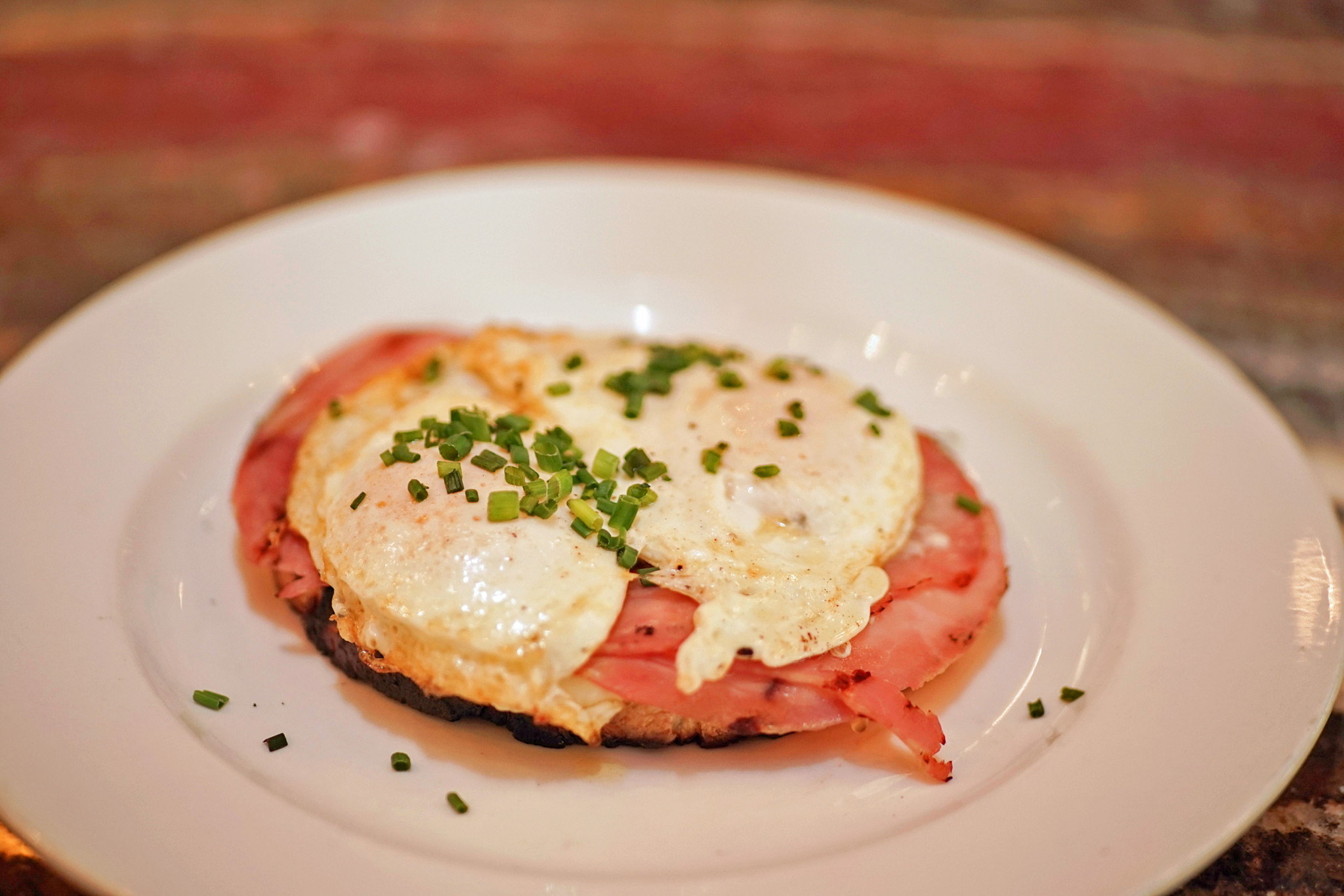 Croque Madame – open-faced sandwich on grilled sourdough with ham de paris, comté cheese béchamel sauce and two over-easy eggs