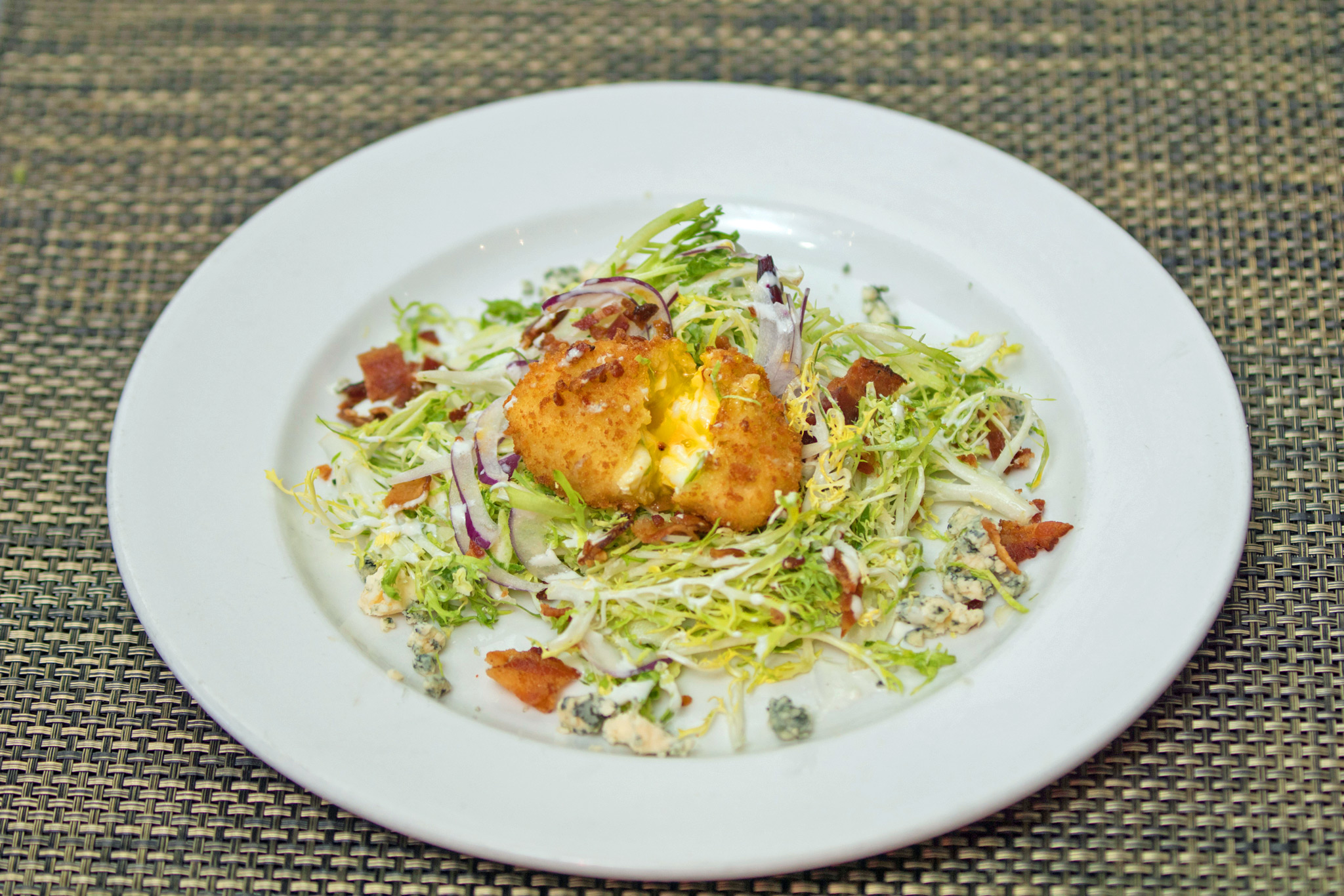 Frisee and Brussel Sprout Salad - crispy poached egg, applewood bacon bits, shaved onion, blue cheese vin