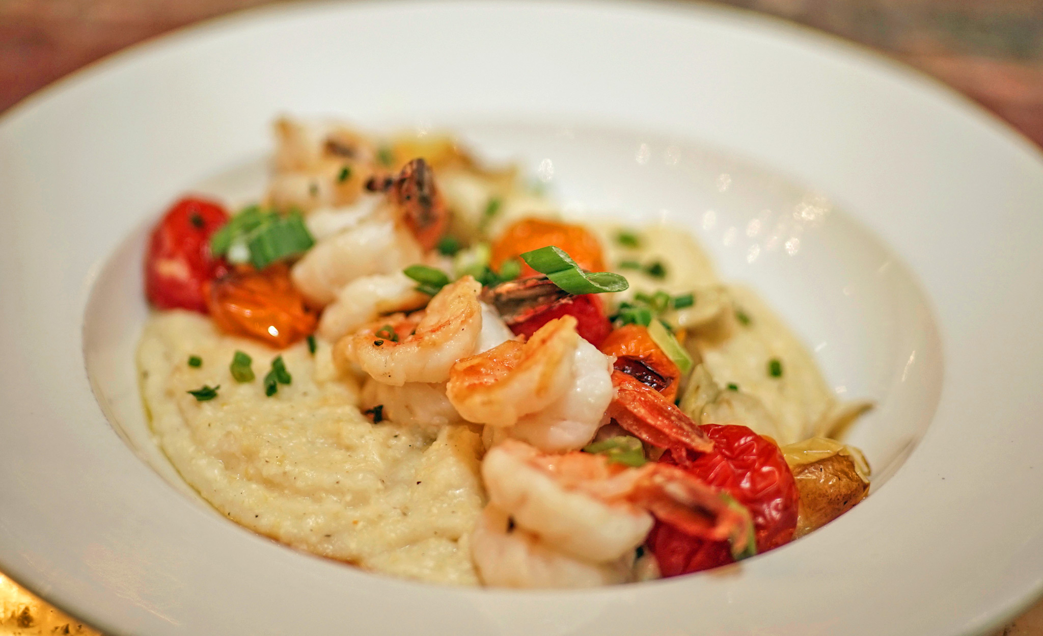 Grilled Shrimp and Grits - aged cheddar and Parmesan grits, roasted tomatoes and fennel