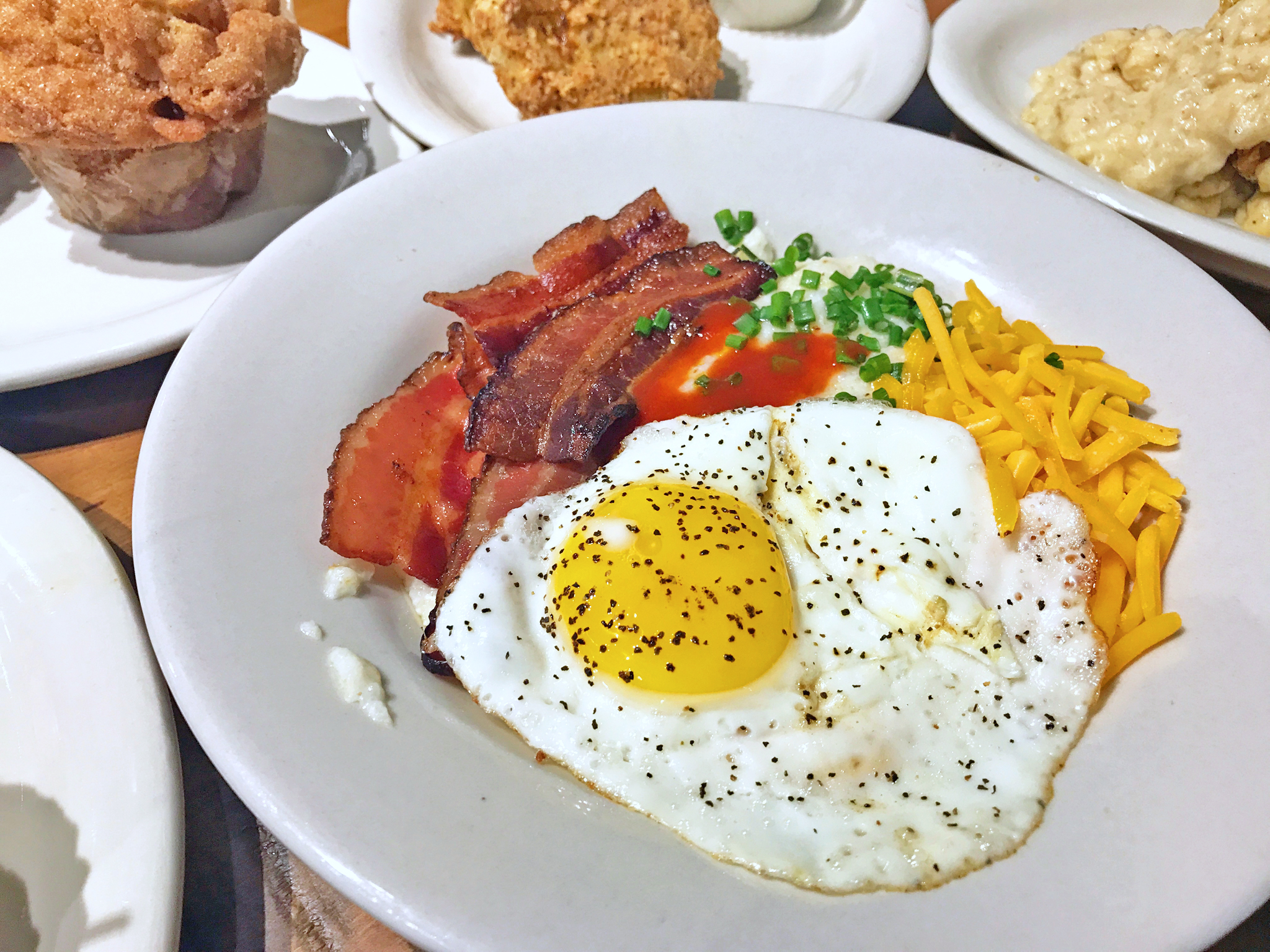 Bluegrass grits cut with cream cheese and butter, topped with pecanwood smoked bacon, cheddar cheese, chives, a sunny side up egg, and a splash of hot sauce.