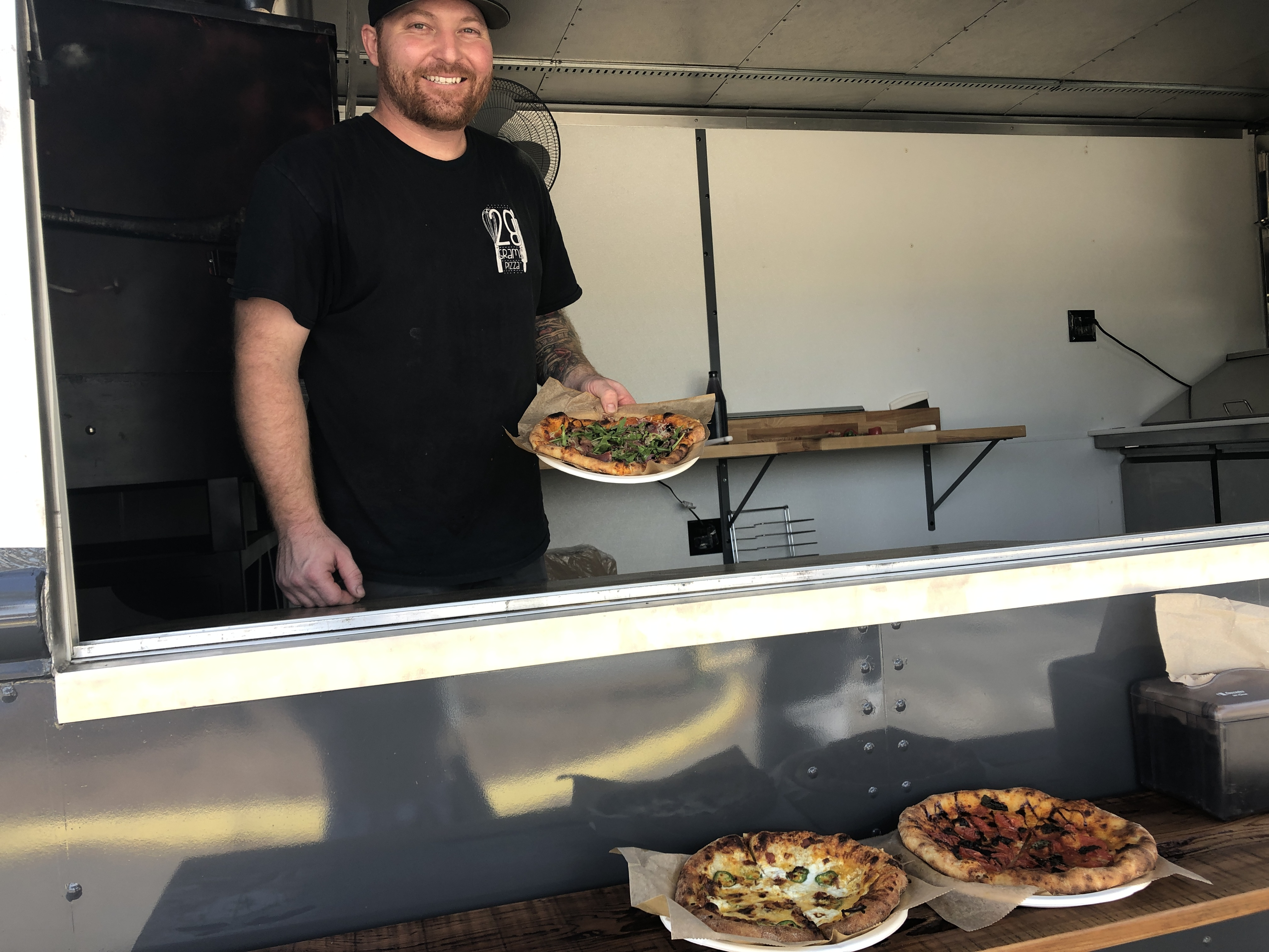 Troy, the owner of 28 Grams, serving up our pizzas