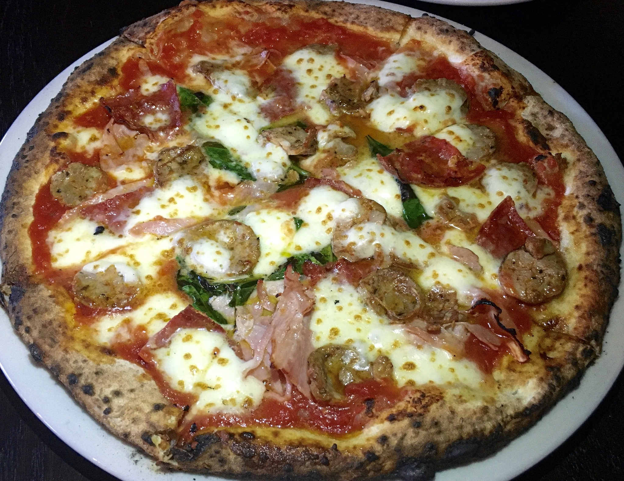 Tre-Carne Pizza with San Marzano Tomato, fior de latte, Soppressata, Prosciutto cotto, spicy Italian Sausage, Basil and Extra-Virgin Olive Oil