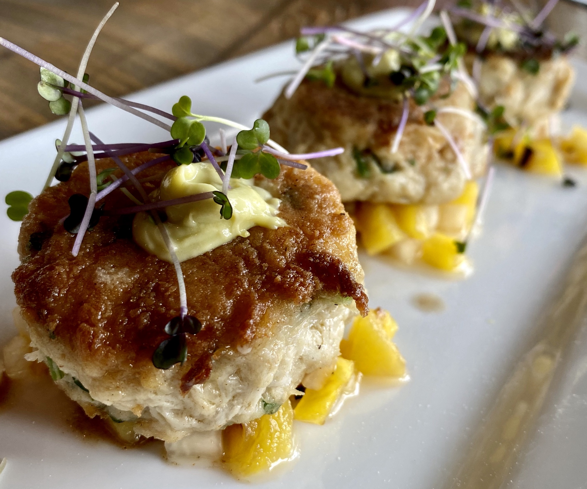 Lump Crab Cakes with grilled pineapple, daikon, kimchi and avaocado crema