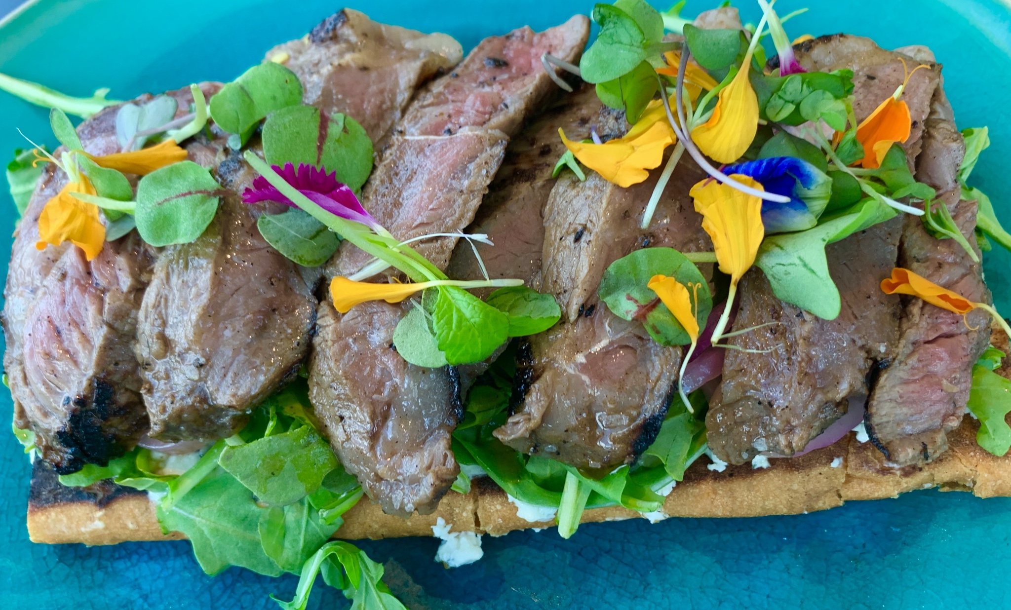 Open Faced Steak Sandwich - mustard vinegar strip steak, pickled red onion, baby arugula, roasted peppers and herbed goat cheese a top a pressed Cuban.