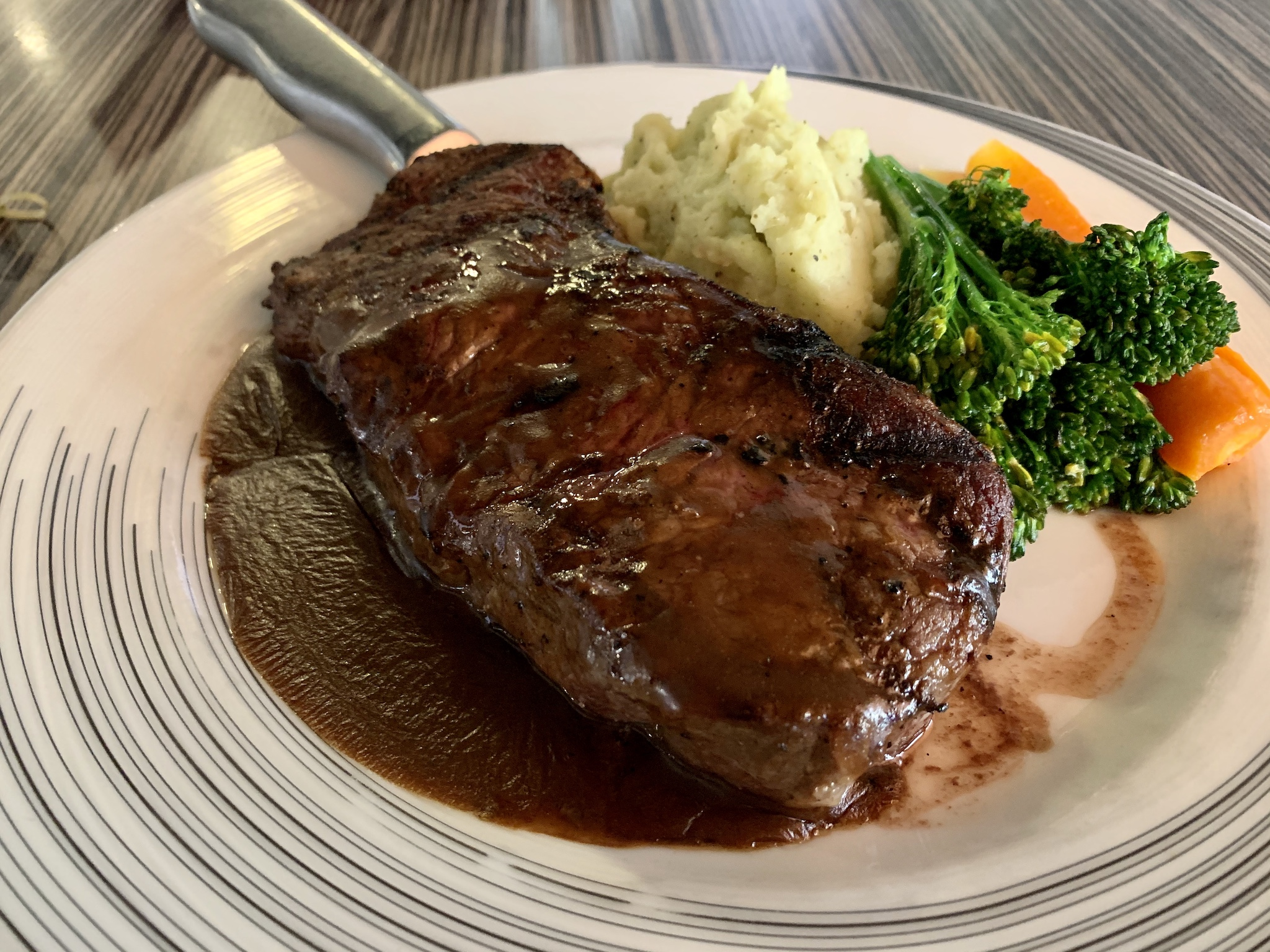 Compass Grille - 10 Oz. Grilled New York Strip with roasted garlic mashed potatoes, chef's choice of vegetables and topped with a demi glaze