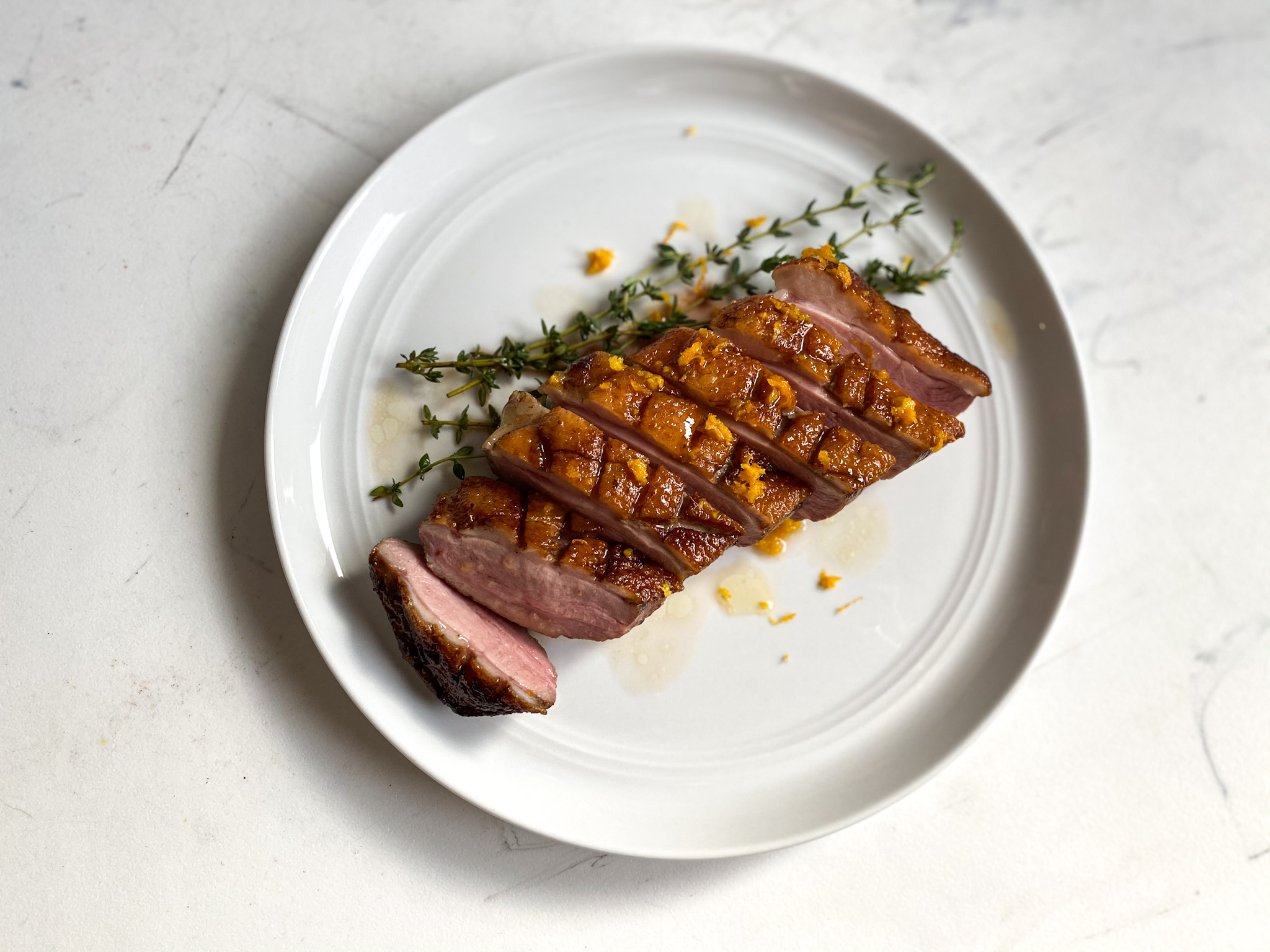 Sliced sous vide duck breast with orange sauce