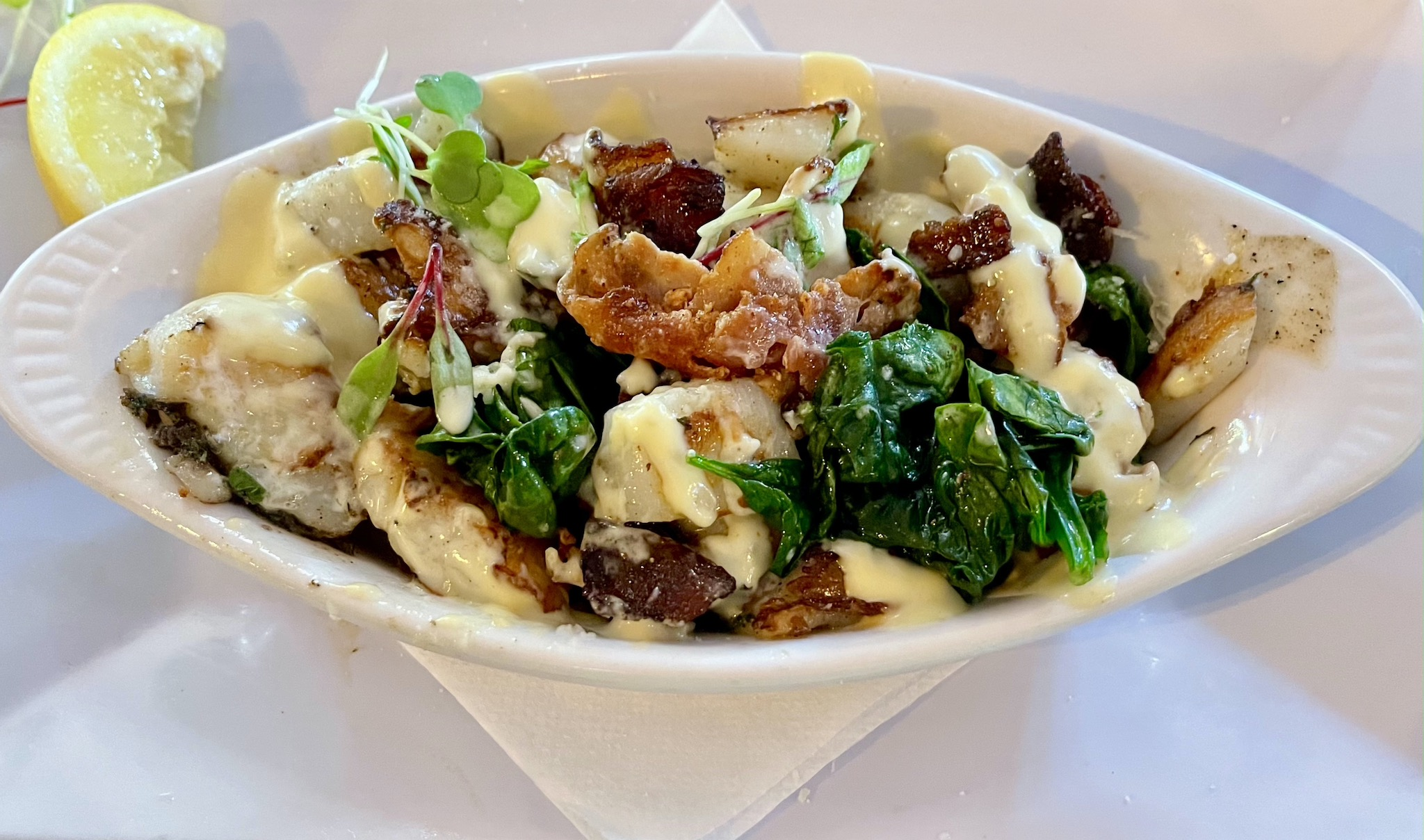 Shrimpys Scallops Rockefeller - Sea scallops sautéed in bacon over grilled spinach with hollandaise & parmesan cheese