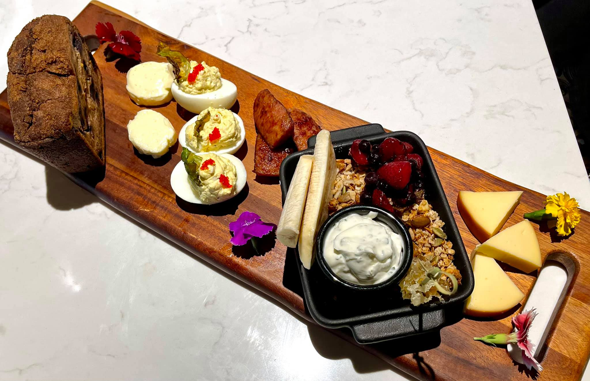 Roost Breakkie Board with Azar Andouille Sausage, Banana-Blueberry Bread, Nut Butter, Granola, Lime Yogurt, Mixed Berries & Banana, Deviled Eggs